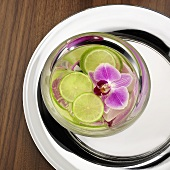 Slices of lime and orchid flower floating in water