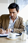 Man with coffee cup writing in personal organizer