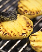 Brushing grilled pineapple with marinade