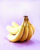 Five bananas on purple background