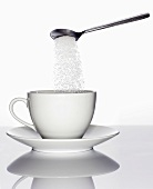 Sugar trickling from a spoon into a cup