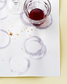 A glass of red wine and glass rings on paper