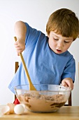 Small boy stirring cake mixture with a wooden spoon