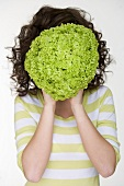 Woman holding a lettuce in front of her face