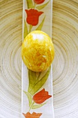 Ein gelbes Osterei auf bedrucktem Band