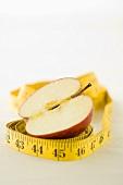 A tape measure around half an apple