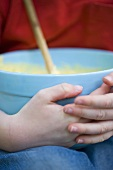 Child's hands holding a bowl of cake mixture