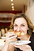 Woman biting into a croissant
