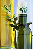 Two bottles of olive oil with olive branch