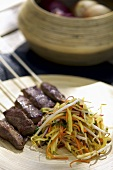 Skewered meat with mango salad