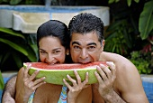 Young couple biting into a slice of watermelon