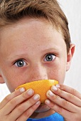 Small boy biting into a wedge of orange