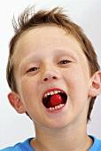 Kleiner Junge mit einem Bonbon im Mund