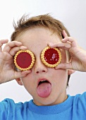 Small boy with two jam tarts