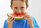 Small boy biting into a slice of watermelon