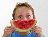 Small boy holding a slice of watermelon