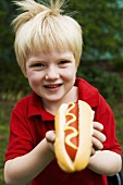 Small boy with a hot dog with mustard