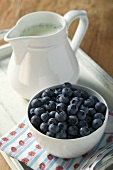 A bowl of blueberries and milk jug