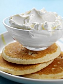 A dish of whipped cream on pancakes