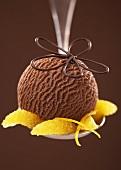 Chocolate ice cream with orange segments on a spoon