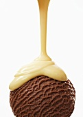 Custard running over a scoop of chocolate ice cream