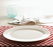 A place-setting with table-mat, plate, cutlery and napkin