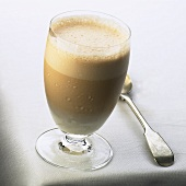 A glass of milky coffee with milk froth