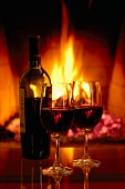 A bottle of red wine with two glasses by the fireside