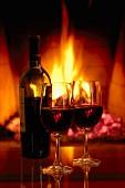 Eine Flasche Rotwein mit zwei Gläsern vor Kamin-Feuer