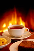 A cup of coffee with cake and biscuits by the fireside