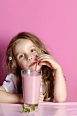 Small girl drinking strawberry milk through a straw