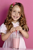 Small girl standing behind a glass of strawberry milk