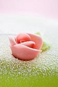 A pink marzipan rose as cake decoration