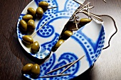 Broken plate with green olives, olive oil and toothpicks