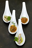 A selection of savoury appetisers served on china spoons