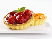 A strawberry tartlet and a peach tartlet