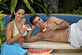Young couple sitting by the pool eating watermelon