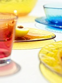 Half a yellow plum and coloured glass tableware