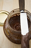 Chocolate spread in a jar with a knife