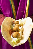 Person holding flatbread filled with falafel (chick-pea balls)