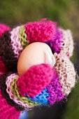 Hände in Wollhandschuhen halten ein frisches Ei