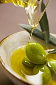 Pouring olive oil over fresh green olives