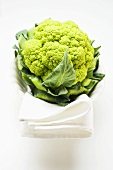 Green cauliflower in bowl with white cloth
