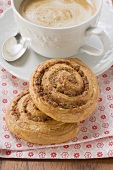 Two cinnamon buns and cup of cappuccino