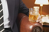 Man holding a glass of whisky
