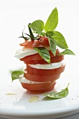 Tower of tomato and mozzarella slices with basil