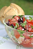 Tomato salad with olives in glass bowl
