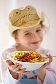 Girl holding plate of spaghetti bolognese