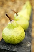 Fresh pears in a row on a wooden structure (close-up)