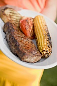 Woman holding plate of grilled beef steak & corn on the cob